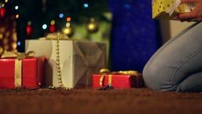 Koppla ihop förälskat ordna gåvor bredvid julträd arkivfilmer