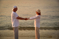 Koppla ihop förälskat på den sandiga stranden i solnedgången Royaltyfria Foton