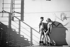 Koppla ihop förälskat på rullarna nära trappan på gatan blA Royaltyfri Bild