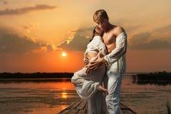 Koppla ihop förälskat på solnedgången royaltyfri fotografi