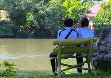 Koppla ihop förälskat sammanträde på bänken vid sjön, sikt för tillbaka sida arkivfoto