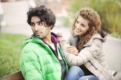 Koppla ihop förälskat sammanträde på en bänk i stad Fotografering för Bildbyråer