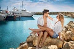 Koppla ihop förälskat sammanträde på stranden nära fartyget Royaltyfri Bild