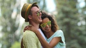 Koppla ihop förälskat skratta, och krama in parkera, hennes armar som slås in runt om hans hals stock video
