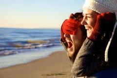 Koppla ihop förälskat spela på solnedgången i vinter på stranden royaltyfri bild