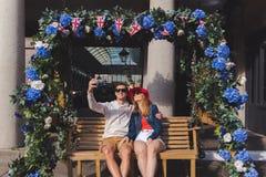 Koppla ihop förälskat ta en selfie som placeras på en svängande bänk i den covent trädgården London royaltyfri bild