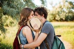Koppla ihop förälskat kyssa med deras ögon som stängs i skog Arkivfoton