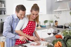 Koppla ihop förälskat laga mat tillsammans i köket och ha gyckel Arkivbilder