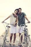 Koppla ihop förälskat skjuta deras cykel tillsammans på en strandpromenad Arkivbilder