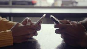 Koppla ihop genom att använda deras mobiltelefoner i kafé arkivfilmer