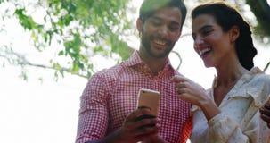 Koppla ihop genom att använda mobiltelefonen, medan ha exponeringsglas av drinken arkivfilmer