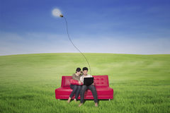 Koppla ihop genom att använda bärbara datorn på den röda soffan med den utomhus- lampan Royaltyfri Foto