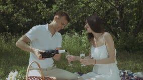 Koppla ihop hällande champagne in i exponeringsglas på picknick lager videofilmer