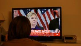 Koppla ihop hållande ögonen på TV efter USA-val som lyssnar till Hillary Clinton anförande arkivfilmer