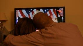 Koppla ihop hållande ögonen på TV efter USA-val som lyssnar till Hillary Clinton anförande lager videofilmer