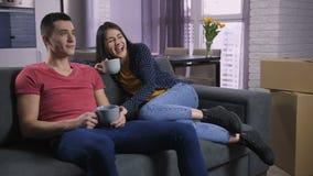 Koppla ihop hållande ögonen på TV, når du har flyttat sig till den nya lägenheten stock video