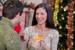 Koppla ihop hållande exponeringsglas med champagne och fira julni Arkivfoto