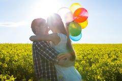 Koppla ihop hållande färgrika ballonger och att omfamna sig i senapsgult fält royaltyfri bild
