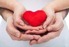 Koppla ihop hållande röd hjärta Arkivfoto
