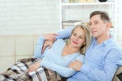 Koppla ihop hemma på soffan som talar och ler royaltyfri foto