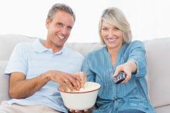 Koppla ihop hållande ögonen på tv och ätapopcorn på soffan Arkivbild