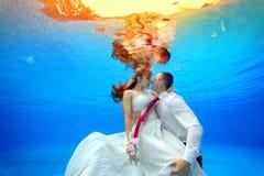 Koppla ihop i bröllopsklänningar som kramar och kysser som är undervattens- i pölen på solnedgången Arkivfoton