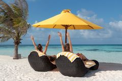 Koppla ihop i br?llopsresa som ligger p? solstolar i Maldiverna Kristallklart bl?tt vatten som bakgrund lyftta armar royaltyfri fotografi