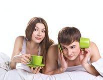 Koppla ihop i en säng med tea kuper Arkivbild