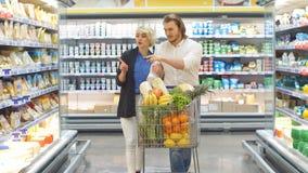 Koppla ihop i en supermarketshopping med livsmedel f?r en k?pande f?r shoppingvagn stock video
