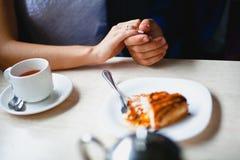 Koppla ihop i ett kafé som rymms av handstycket av kakan Royaltyfri Bild