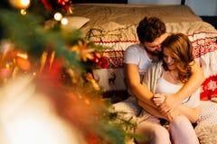 Koppla ihop in i pyjamas som vilar på golvet bredvid sängen nära julgranen Royaltyfria Bilder