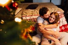 Koppla ihop in i pyjamas som vilar på golvet bredvid sängen nära julgranen Royaltyfri Foto