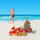 Koppla ihop i santa hattar på den tropiska stranden med julträdet och Arkivfoto