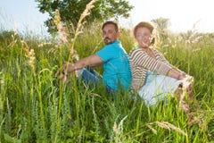 Koppla ihop i stort grönt gräs tillbaka för att dra tillbaka Man- och kvinnasammanträde i fältet i sommardag älska gossipin för p Royaltyfria Bilder