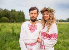 Koppla ihop i traditionell klänning för ryss på ängen Arkivfoto