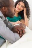 Koppla ihop i vardagsrum som talar, medan sitta på soffan Arkivbild