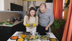 Koppla ihop inställning av tabellen för en matställe tillsammans Frun drar från ugnen bakade aromatiska hönan och sätter den på arkivfilmer