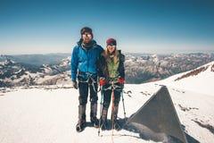 Koppla ihop klättrare man och kvinnan nådd Elbrus bergtoppmöte arkivfoton