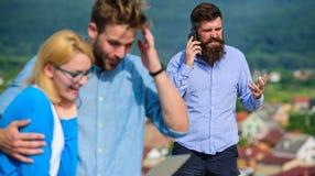 Koppla ihop kollegor som flörtar medan framstickandet som är upptaget med mobil konversation Par som har gyckel medan surfa för i fotografering för bildbyråer