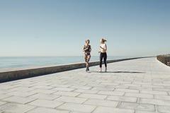 Koppla ihop kvinnlig spring som övar att jogga som är lyckligt på strand Arkivbilder