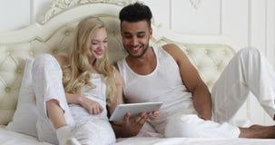 Koppla ihop liggande säng genom att använda minnestavladatoren, sovrum för morgon för leende för kvinna för blandningloppman arkivfilmer