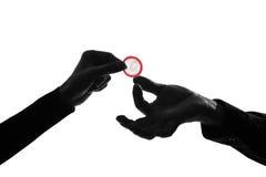 Koppla ihop man- och kvinnahänder som rymmer att ge kondomen nära övre Royaltyfri Fotografi