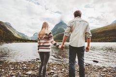 Koppla ihop man- och kvinnainnehavhänder som tycker om berg och sjösikt arkivfoto
