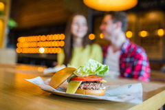 Koppla ihop mannen och kvinnan - att äta hamburgaren och att dricka i en snabbmatmatställe; fokusera på målet arkivbild