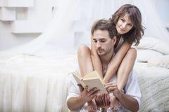 Koppla ihop mannen och kvinnan hemma i säng med en bok och en varm drink arkivbild
