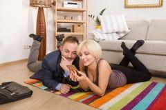 Koppla ihop mannen och kvinnan som hemma ligger på golv Royaltyfri Fotografi