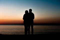 Koppla ihop mannen och kvinnan som kramar förälskat bli på stranden Royaltyfri Bild