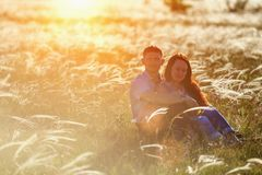 Koppla ihop mannen och kvinnan som kramar sammanträde i natur i gräset i solen arkivfoton