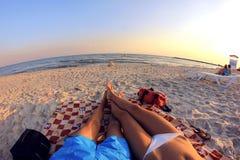 Koppla ihop mannen och kvinnan som solbadar på stranden som förbiser havet Royaltyfri Bild
