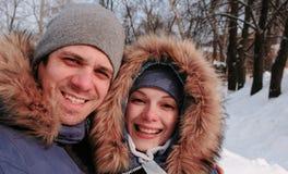 Koppla ihop mannen, och kvinnan som talar på video anslutning och går i vinterstad, parkerar i snöig dag med fallande snö royaltyfri bild